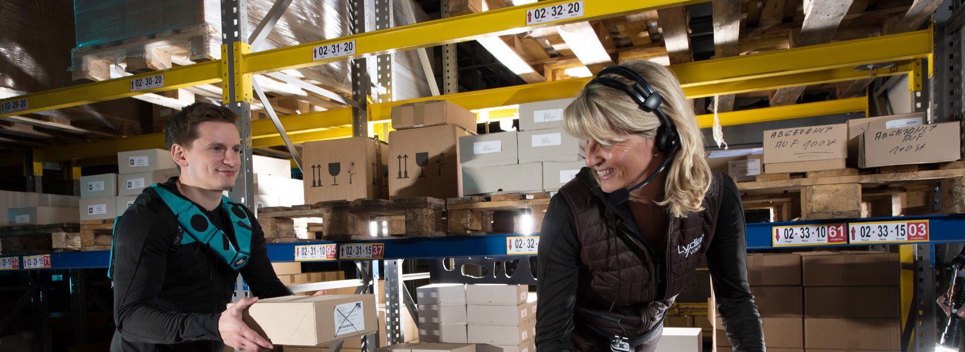 Two Warehouse Workers Are Picking By Voice With A Headset And With The Lydia VoiceWear Vest.